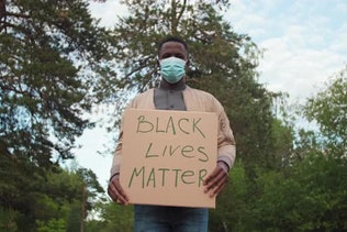 African-American Man in Face Mask Protesting with BLM Sign