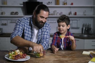 Caring Dad and Son Making Delicious Fruit Kebabs